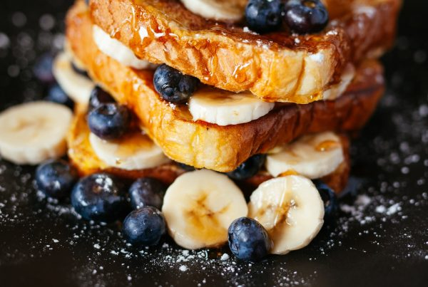 A plate of french toast with blueberry and banana